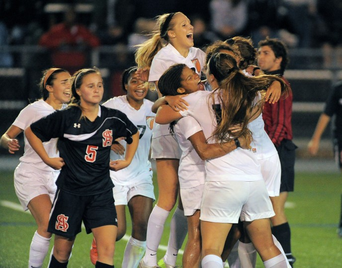 McDonogh forward Bridgette Andrzejewski (above) celebrates with her teammates behind Spalding defender Caroline Mullin, who walks off the field after time expires in the 2013 IAAM Girls' Soccer Championship at Siegert Field. The Eagles held on to win, 2-1. (Karl Merton Ferron/Baltimore Sun)