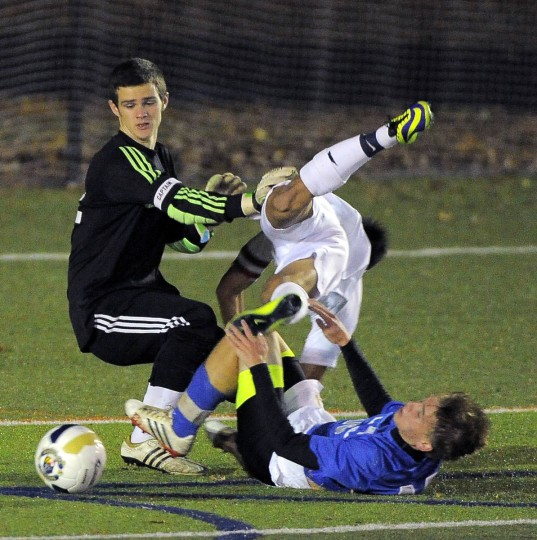 Severna Park forward Daniel Kwon tumbles over Leonardtown's Matt Wolfe (on turf) as goalkeeper Trevor Young turns to chase after the ball as it heads for the front of the goal. (Karl Merton Ferron/Baltimore Sun)
