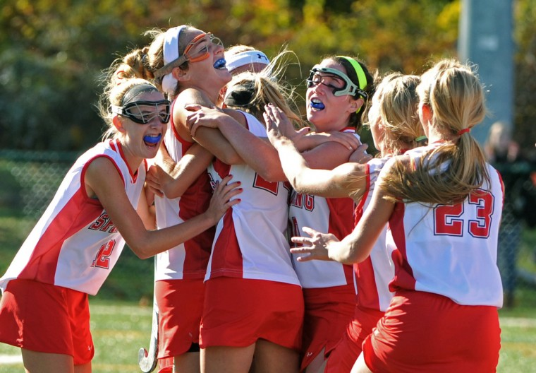 Spalding players crowd around Erin Shanahan, second from left, who scored the game-winning goal in OT, giving the Cavaliers a 2-1 win over McDonogh in the IAAM A Conference field hockey title game. (Amy Davis/Baltimore Sun)