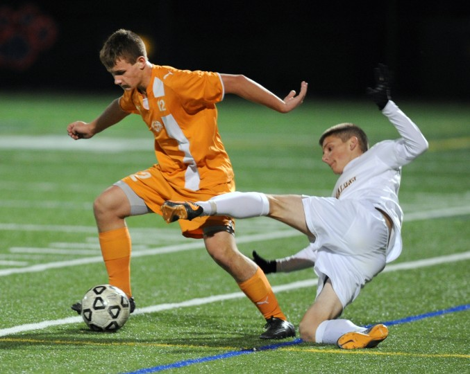 South Carroll's Tyler Britt loses his balance and falls still trying to block Fallston's Matt Estremsky as he takes the ball during Saturday's Class 2A state semifinal game at Bel Air High School. (Matt Button/BSMG)