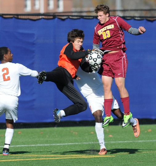 Oakland Mills goalie Duncan Rheingans-Yoo gets up to make the save as Hereford's Matt Groff stays close during Saturday's Class 2A boys soccer state semifinal game at Bel Air High School. (Matt Button/BSMG)