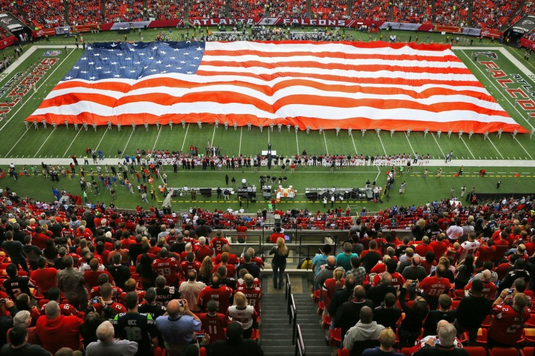 "Fans stand for the national anthem as approximately 100 soldiers from the Georgia Army National Guard unfold a giant American flag to commemorate Veteran's Day in a ""Salute to Service,"" before the game between the Atlanta Falcons and Seattle Seahawks at the Georgia Dome in Atlanta, Sunday, Nov. 10, 2013. (Curtis Compton/Atlanta Journal-Constitution/MCT)"