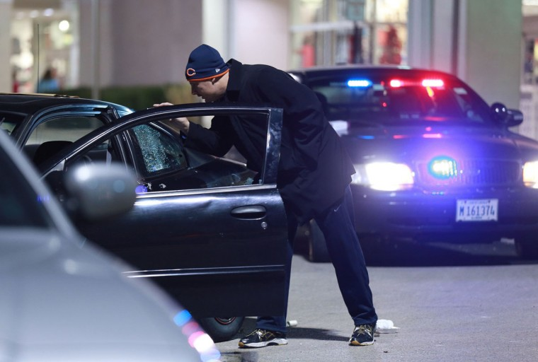 A detective investigates the scene of a police-involved shooting outside Kohl's department store on Weber Road in Romeoville, Ill., Nov. 28, 2013. A theft attempt by two or more suspects resulted in police action and the shooting scene outside the store. (John J. Kim/Chicago Tribune/MCT)