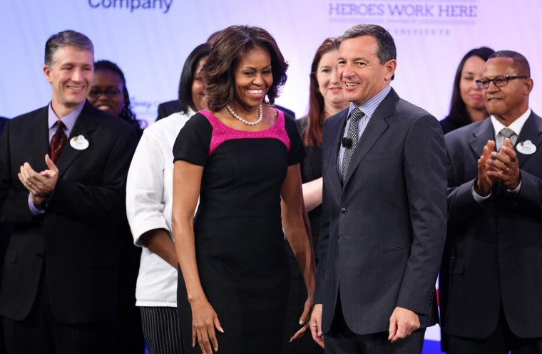 First lady Michelle Obama is welcomed to the stage by Disney Co. CEO Bob Iger, center right, during Disney's Veterans Institute luncheon, at the Boardwalk Inn at Walt Disney World in Lake Buena Vista, Fla., Thursday, Nov. 14, 2013. (Joe Burbank/Orlando Sentinel/MCT)