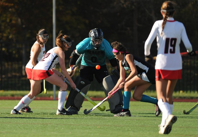 Jensyn Koontz of North Carroll, left, and Linnea Gonzalez of Patterson Mill, right, battle for the ball as Patterson Mill goalie Maddie Hedrick tries to kick it away during the Class 1A state field hockey championship game at Washington College in Chestertown on Saturday, November 9, 2013. (Brian Krista/BSMG)