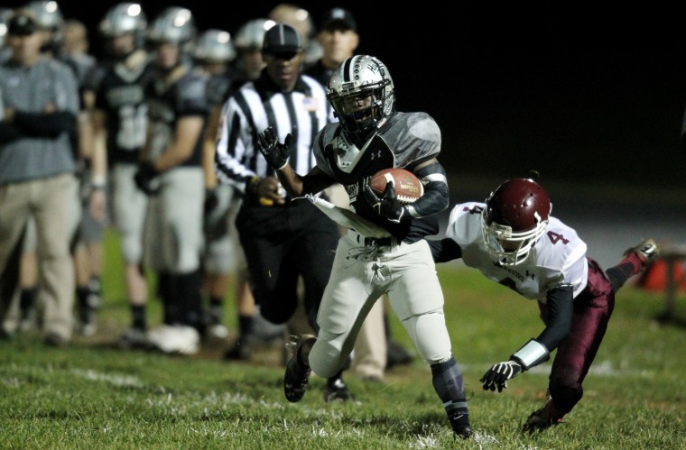 Patterson Mill's Devinn Fisher, center, carries the ball while Harve de Grace's Geno Nappi, dives for the tackle during the football game at Patterson Mill High School in Bel Air on Friday, Nov. 1, 2013. (Jen Rynda/BSMG)