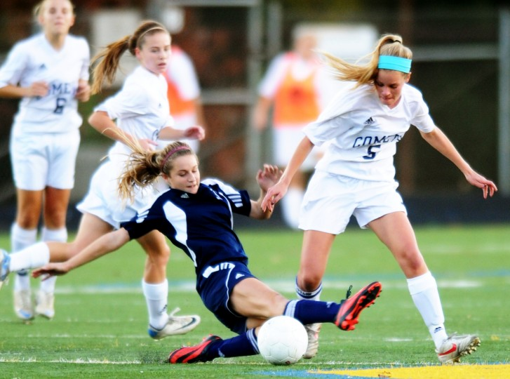 Perry Hall's Rachel Bohli, left, slides into Catonsville's Katie Viets in an attempt to steal possession during the regional semifinal soccer match at Catonsville High School in Catonsville on Friday, Nov. 1, 2013. (Jon Sham/BSMG)