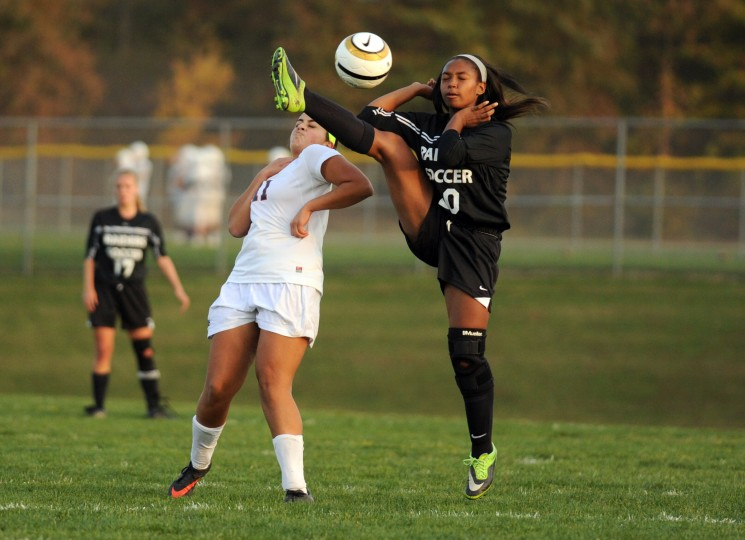 Jaylyn Chandler of Atholton narrows misses contact with Lilly Hermina of Reservoir as she makes a high kick on the ball during a girls soccer playoff game at Reservoir High School on Tuesday, Oct. 29, 2013. (Brian Krista/BSMG)