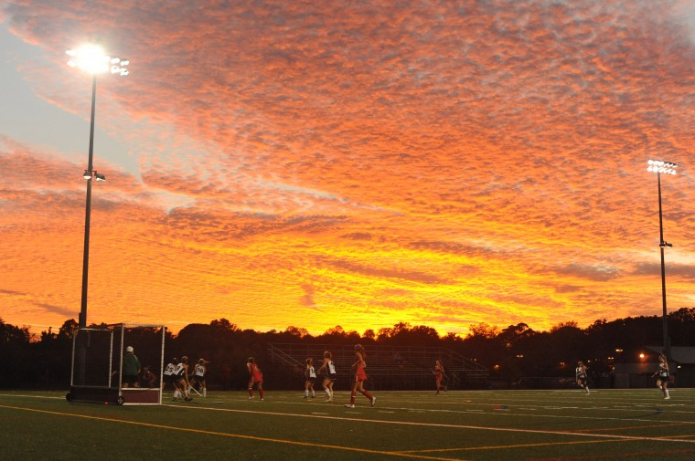 Glenelg and Century field hockey players compete underneath a layer of clouds dramatically colored by the setting sun during the 2A state semifinal field hockey game at Broadneck High School on Wednesday, November 6, 2013. (Brian Krista/BSMG)