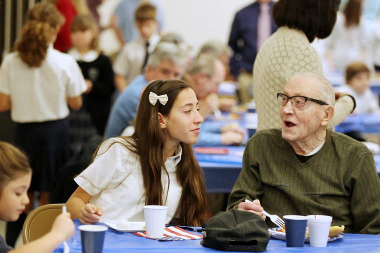 Morgan Flack, 13, of Ellicott City talks to her grandfather Korean War Army Veteran Anthony D'Eramo, right, of Ellicott City during a breakfast for Veterans Day at Resurrection-St. Paul School in Ellicott City, MD on Monday, November 11, 2013. (Jen Rynda/BSMG)