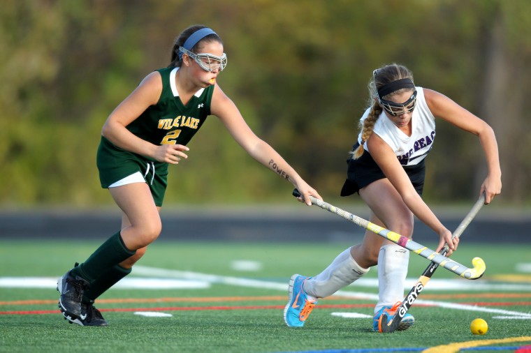 Wilde Lake's Marissa Sciabarra, left, tries to slow down Long Reach's Alina Milauskas, right, during the field hockey playoff game at Long Reach High School in Columbia on Monday, Oct. 28, 2013. (Jen Rynda/BSMG)
