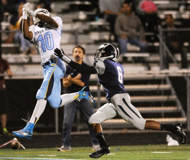 A pass intended for River Hill's Jonathan Kanda, left, slips right through his fingers as Howard's Kyle Walker is ready to bring him down during a football game at Howard High School in Ellicott City on Friday, Nov. 1, 2013. (Jon Sham/BSMG)
