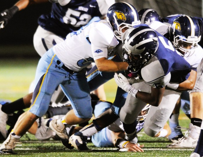 Howard running back Jamil Campbell, center, gets wrapped up by River Hill defensemen during a football game at Howard High School in Ellicott City on Friday, Nov. 1, 2013. (Jon Sham/BSMG)