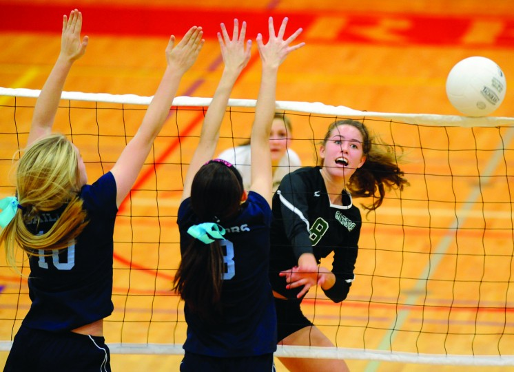 St. Paul's School for Girls' Kendall Burdette, right, hits a ball as Mount de Sales' Emily Smith, left, and Lynn Walsh, center, defend the net in the second game of the IAAM A Conference volleyball championship match Saturday, Nov. 2, 2013 at Roland Park Country School in Baltimore. (Photo by Steve Ruark)