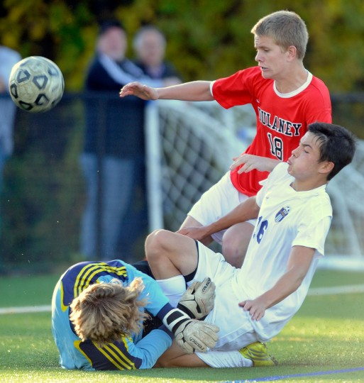 Dulaney goalkeeper Patrick Larkin, left, and teammate Shane Grogan, center, defend against Perry Hall's Andrew Yu in the second half of a Class 4A regional semifinal soccer game Friday, Nov. 1, 2013, in Perry Hall. (Photo by Steve Ruark)