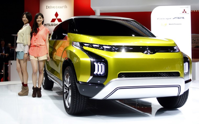 Models pose next to a Mitsubishi Motors Corp AR concept car at the 43rd Tokyo Motor Show November 20, 2013. Fourteen Japanese and 18 overseas carmakers and motorcycle manufacturers are participating in the Tokyo Motor Show, which kicked off on Wednesday for the media. (Yuya Shino/Reuters)