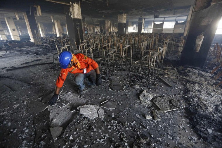 A firefighter inspects the damage at a Standard Group garment factory which was on fire in Gazipur November 29, 2013. A huge fire on Friday destroyed the Bangladesh garment factory supplying key Western brands, authorities said, in a blaze touched off by workers angered over rumours of a colleague's death in police firing. There were no initial reports of casualties in the fire. Police broke up a clash with the workers with tear gas, but hundreds of workers gathered later, vandalized the factory, set two buildings on fire, and blockaded the road, said Mushfiqur Rahman, a manager at Standard Garments, a firm in the building. (Andrew Biraj/REUTERS)