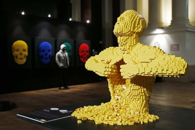 """The art work titled """"Yellow,"""" which is made out of Lego bricks, is seen as a visitor poses next to another Lego art work titled """"Skulls"""" (L) during """"The Art of the Brick"""" exhibition at the Brussels Stock Exchange November 25, 2013. The exhibition featuring large Lego art works by U.S. Lego artist Nathan Sawaya will run till April 21, 2014. (Francois Lenoir/Reuters)"""