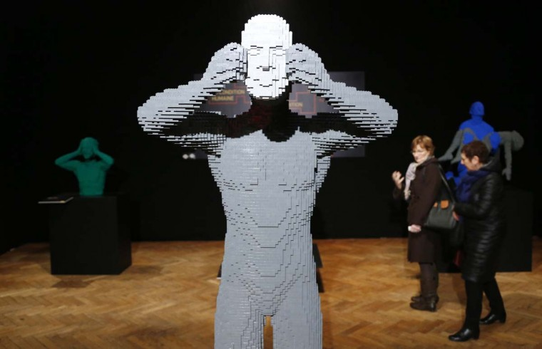 """Visitors walk behind the art work titled """"Mask,"""" constructed out of 18,509 Lego bricks, during """"The Art of the Brick"""" exhibition at the Brussels Stock Exchange November 25, 2013. The exhibition featuring large Lego art works by U.S. Lego artist Nathan Sawaya will run till April 21, 2014. (Francois Lenoir/Reuters)"""