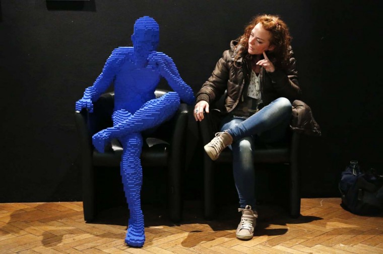 """A visitor poses beside the art work titled """"Blue Guy Sitting"""" made out of Lego bricks during the """"The Art of the Brick"""" exhibition at the Brussels Stock Exchange November 25, 2013. The exhibition featuring large Lego art works by U.S. Lego artist Nathan Sawaya will run till April 21, 2014. (Francois Lenoir/Reuters)"""
