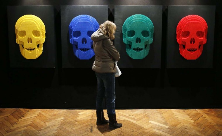 """A visitor looks at the art work titled """"Skulls,"""" which is constructed out of 12,444 Lego bricks, during the """"The Art of the Brick"""" exhibition at the Brussels Stock Exchange November 25, 2013. The exhibition featuring large Lego art works by U.S. Lego artist Nathan Sawaya will run till April 21, 2014. (Francois Lenoir/Reuters)"""