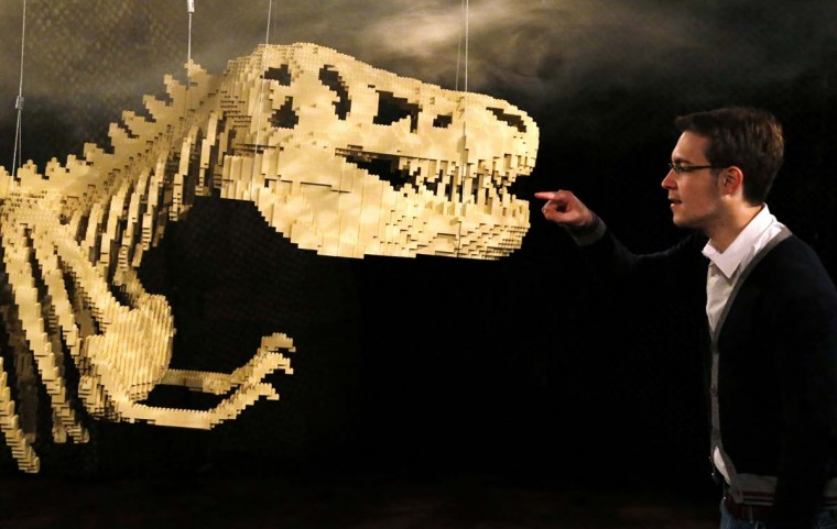 """A visitor looks at the art work titled """"Dinosaur Skeleton,"""" which is constructed out of 80,020 Lego bricks, during the """"The Art of the Brick"""" exhibition at the Brussels Stock Exchange November 25, 2013. The exhibition featuring large Lego art works by U.S. Lego artist Nathan Sawaya will run till April 21, 2014. (Francois Lenoir/Reuters)"""
