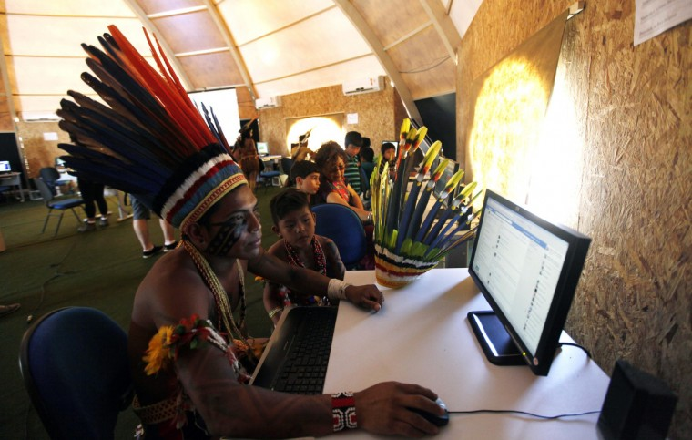 Brazilian indigenous people use computers inside a tent during the XII Games of the Indigenous People in Cuiaba November 13, 2013. Forty-eight Brazilian Indigenous tribes will present their cultural rituals and compete in traditional sports such as archery, running with logs and canoeing during the XII Games of Indigenous People which will run until November 16. (Paulo Whitaker/Reuters)