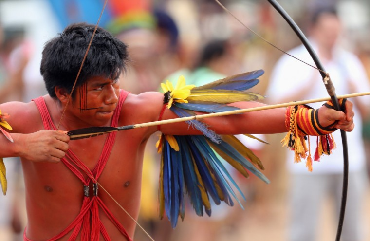 A member of the Brazilian indigenous ethnic group Bororo aims his arrow during the bow-and-arrow competition at the XII Games of the Indigenous People, in Cuiaba November 12, 2013. Forty eight Brazilian Indigenous tribes will present their cultural rituals and compete in traditional sports such as archery, running with logs and canoeing during the XII Games of Indigenous People which will run until November 16. (Paulo Whitaker/Reuters)