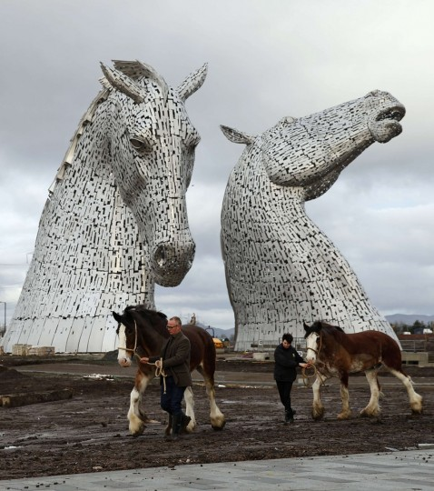 Scottish sculptor Andy Scott (L) and Donna Auchinvole lead Clydesdale horses Duke and Baron, in front of The Kelpies, two 30 meter high stainless-plate horse heads in Falkirk, Scotland November 27, 2013. The horses were the models for the sculptures, part of a £41 million GB pounds Helix regeneration project. (Russell Cheyne/REUTERS)