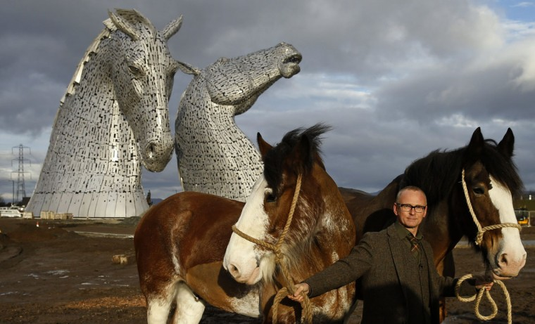 Scottish sculptor Andy Scott stands with Clydesdale horses Duke and Baron, in front of The Kelpies, two 30 meter high stainless-plate horse heads in Falkirk, Scotland November 27, 2013. The horses were the models for the sculptures, part of a £41 million GB pounds Helix regeneration project. (Russell Cheyne/REUTERS)