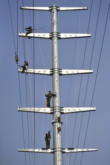 Employees work on a pylon in Hefei, Anhui province. China needs to sustain economic growth of 7.2 percent to ensure a stable job market, Premier Li Keqiang said as he warned the government against further expanding already loose money policies. In one of the few occasions when a top official has specified the minimum level of growth needed for employment, Li said calculations show China's economy must grow 7.2 percent annually to create 10 million jobs a year. (Reuters)