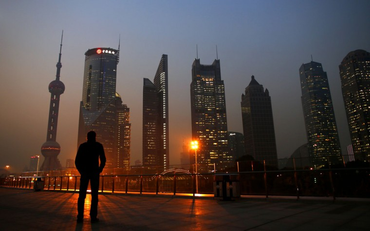 A man looks at the Pudong financial district of Shanghai November 20, 2013. With a shift in tone and language, China's central bank governor has dangled the prospect of speeding up currency reform and giving markets more room to set the yuan's exchange rate as he underlines broader plans for sweeping economic change. The central bank under Zhou Xiaochuan has consistently flagged its intention to liberalise financial markets and allow the yuan to trade more freely, even before the Communist Party's top brass unveiled late last week the boldest set of economic and social reforms in nearly three decades. (Carlos Barria/REUTERS)