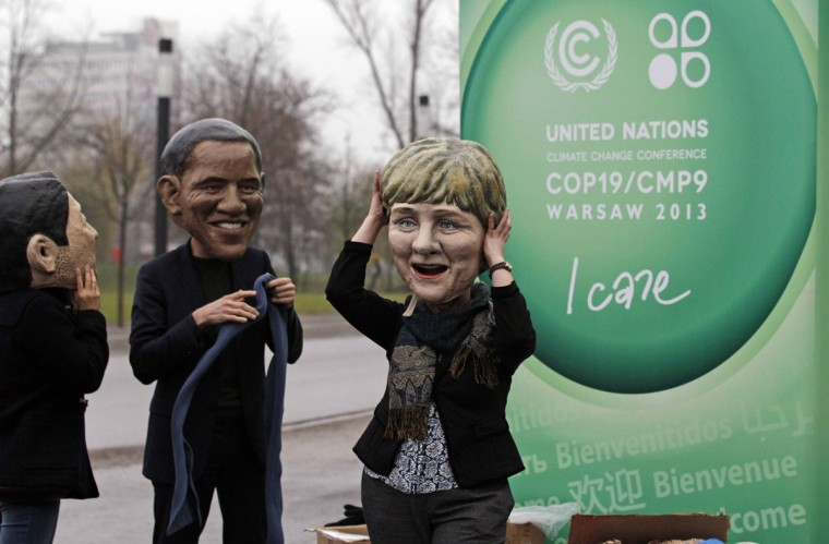 A protester adjusts her mask of German Chancellor Angela Merkel next to fellow protesters wearing masks of Japan's Prime Minister Shinzo Abe (L) and U.S. President Barack Obama (C) in front of a sign of the United Nations Framework Convention on Climate Change (COP19) on the last day of the conference in Warsaw November 22, 2013. The event staged by Oxfam called on more decisive action from world leaders in 2014 after few concrete steps have emerged from two weeks of climate talks in Warsaw, according to media reports. (REUTERS/Kacper Pempel)