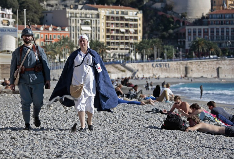 Two World War One Historical Association members dressed as a nurse and Poilu (French soldiers from World War I) walk on the beach before an Armistice ceremony at the war memorial in Nice November 11, 2013. The year 2014 will mark the centennial commemoration for the soldiers who fought in the first World War. (Eric Gaillard/Reuters)