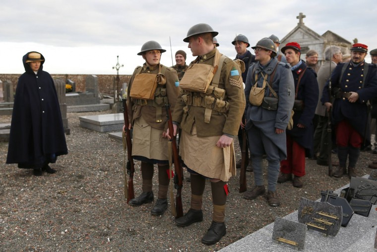 """World War One Historical Association """"14-18 en Somme"""" members Benoit (C) and Aurelien (R) wearing Canadian vintage army uniforms lead a pack of members after a ceremony at the military cemetery of Lamothe-Warfusee, Northern France, November 10, 2013. The historical association """"14-18 en Somme"""" was created in August 2009 by French history teacher Sylvain Pinard with the aim of keeping alive the memory of the soldiers of World War One, and promoting understanding of the battles of the Great War. Armed with their motto """"Never forget, always remember"""", the 30 members live, eat and sleep in the same conditions as the soldiers of 1914-18. Throughout the year, they take part in official ceremonies and Remembrance Day celebrations, camps, exhibitions in villages and debates in schools and are sought-after as extras for war films. The association has received a lot of requests for the year 2014 which will mark the 100th anniversary of the start of the First World War. Picture taken November 10, 2013. (Charles Platiau/REUTERS)"""