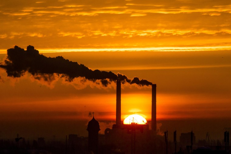 The sun rises behind the billowing chimneys of a power station in Berlin. (Thomas Peter/Reuters)
