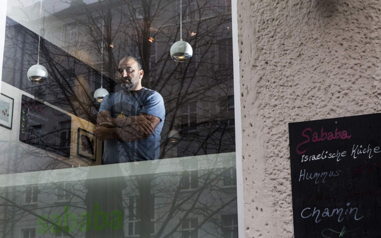 """Israeli Jewish cafe owner Ze'er Avrahami poses in the window of his Israeli cafe """"Sababa"""" in the Prenzlauer Berg district of Berlin November 7, 2013. """"I came to Berlin initially for the same reason everyone comes to Berlin, its cheap and there are many parties. But if you are Jewish there is another layer to Berlin you have to explore. Berlin has to do with death of Jewish people. This is the layer of Jewish life that used to exist here in the past. No body talks about it. There was good life here, very intelligent and cultural life. The right life for a Jewish person doesn't have to do with a nation. The right life is when you live in the diaspora. This is how Jews are supposed to live. My concern is the continuation of Jewish life in the diaspora. What does it mean to live in the diaspora, as a minority? The thrive to be successful. You have to be successful, intelligently, financially. This is lost in Israel where you have nothing to prove,"""" Avrahami said. November 9th marks the 75th anniversary of the 'Kristallnacht' ('crystal night' or also referred to as 'night of broken glass') when Nazi thugs conducted a wave of violent anti-Jewish pogroms on the streets of Berlin and other cities in 1938. (Thomas Peter/REUTERS)"""