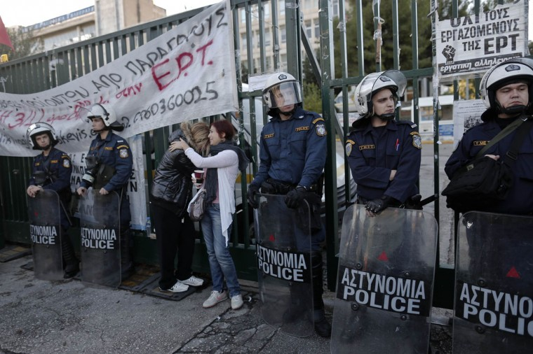 Former employees of the Greek state television ERT comfort each other outside its headquarters at Agia Paraskevi suburb north of Athens November 7 ,2013. Greek riot police stormed the building of former state television ERT on Thursday and evicted dozens of protesters occupying it since June when the government abruptly shut the broadcaster, police officials said. Scuffles broke out between some protesters and riot police, who had cordoned off the area and blocked the entrance to the building. (John Kolesidis/REUTERS)