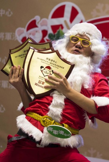 """Plato Chan, who calls himself """"Santa Banana,"""" reacts after winning a competition, to determine who will represent Hong Kong at the annual Santa Claus Winter Games, at a shopping mall in Hong Kong November 1, 2013. Hong Kong won the championship in 2009 and came in second in 2012 for the international competition which will commence on November 23 in Gaellivare, Sweden. (Tyrone Siu/Reuters)"""