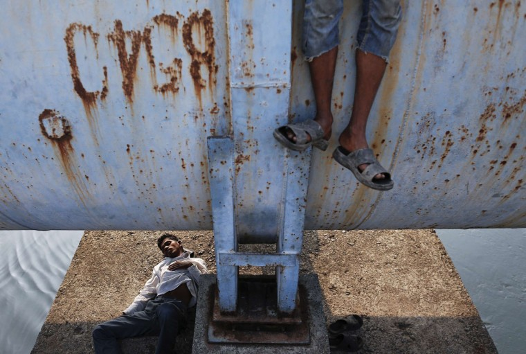 A man sleeps under a water pipeline as another stands on it in Mumbai November 7, 2013. (Danish Siddiqui/REUTERS)