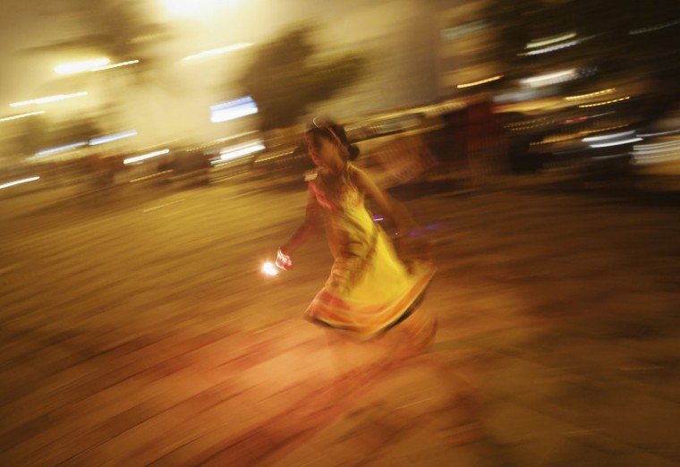 A girl runs with a firecracker, celebrating the Hindu festival of Diwali, the annual festival of lights, in Mumbai November 3, 2013. (Danish Siddiqui/Reuters)