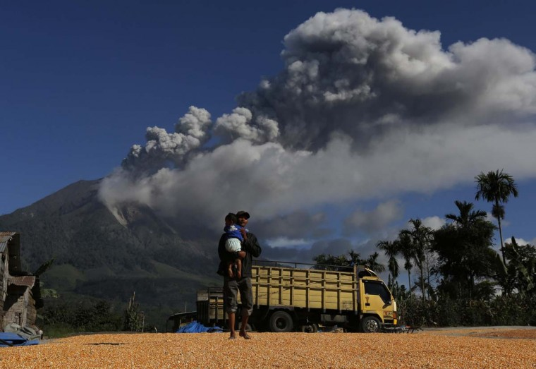 A man holds his son while walking on dried corn with Mount Sinabung spewing ash in the background at Sibintun village in Karo district, Indonesia's North Sumatra province November 25, 2013. Indonesia ordered the evacuation of 15,000 residents near the active volcano in the west of the vast archipelago on Sunday as authorities raised the alert for the emergency to the highest level.(Beawiharta/Reuters)
