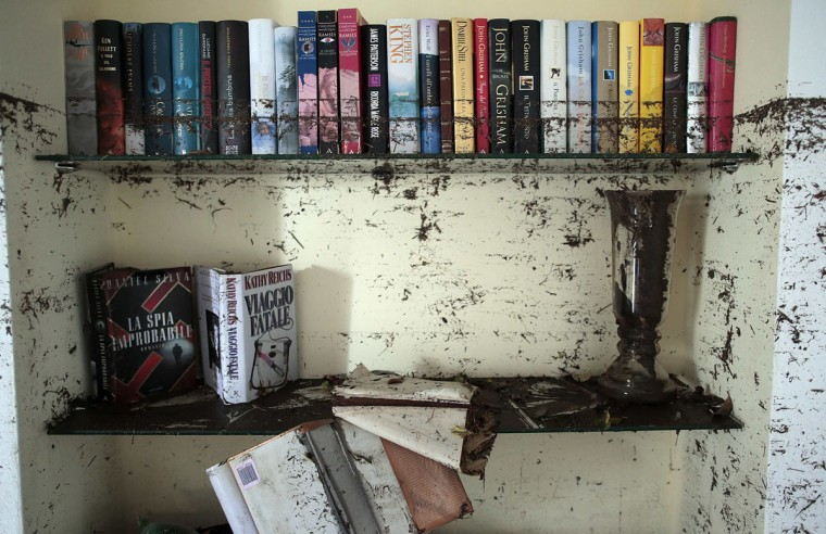 Dirtied books are seen in a flooded house following extreme rainfall in Olbia on Sardinia island November 20, 2013. A cyclone killed 18 people and made hundreds homeless as extreme rainfall flooded eastern parts of the Mediterranean island of Sardinia, Italian authorities said on Tuesday. The government declared a state of emergency after Cyclone Cleopatra dropped 450mm of rain in an hour and a half overnight, causing rivers to burst their banks, sweeping away cars and flooding homes across the island. (Tony Gentile/REUTERS)