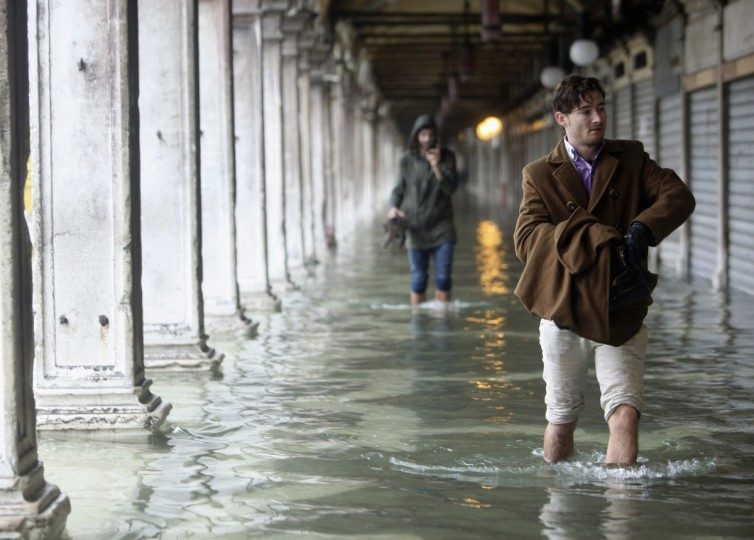 People walk through flooded St. Mark's Square during a period of seasonal high water in Venice. (Manuel Silvestri/Reuters)