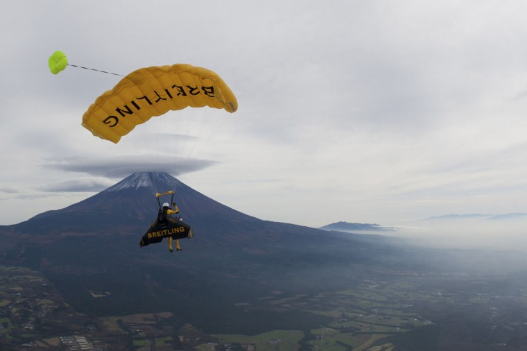 """Yves Rossy, known as the Jetman, parachutes after flying in front of Mount Fuji in this November 3, 2013 handout photograph released by Breitling SA. The Swiss aviator dropped from a helicopter and deployed the jet-powered carbon-kevlar """"Jetwing"""" and uses his body to steer as he flew near Mt. Fuji nine times between October 28 and November 3. (Katsuhiko Tokunaga/REUTERS)"""