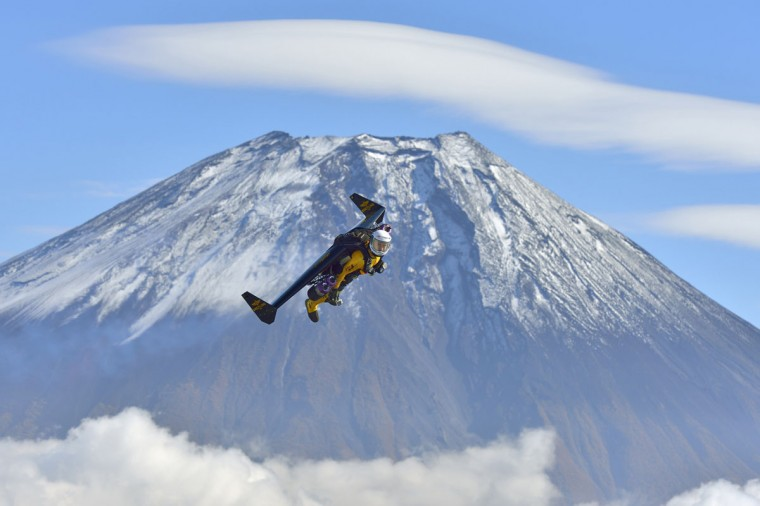 """Yves Rossy, known as the Jetman, flies in front of Mount Fuji in this November 1, 2013 handout photograph released by Breitling SA. The Swiss aviator dropped from a helicopter and deployed the jet-powered carbon-kevlar """"Jetwing"""" and uses his body to steer as he flew near Mt. Fuji nine times between October 28 and November 3. (Katsuhiko Tokunaga/REUTERS)"""