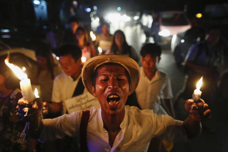 A demonstrator holds candles during a protest against the government's decision to raise electricity prices in Yangon. (Soe Zeya Tun/Reuters)