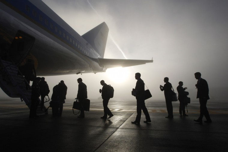 Traveling White House staff and press board the rear steps of Air Force One on a foggy morning in Seattle, November 25, 2013. U.S. President Barack Obama is attending fundraisers and events on the economy and immigration in Los Angeles and San Francisco on Monday. (REUTERS/Jason Reed)