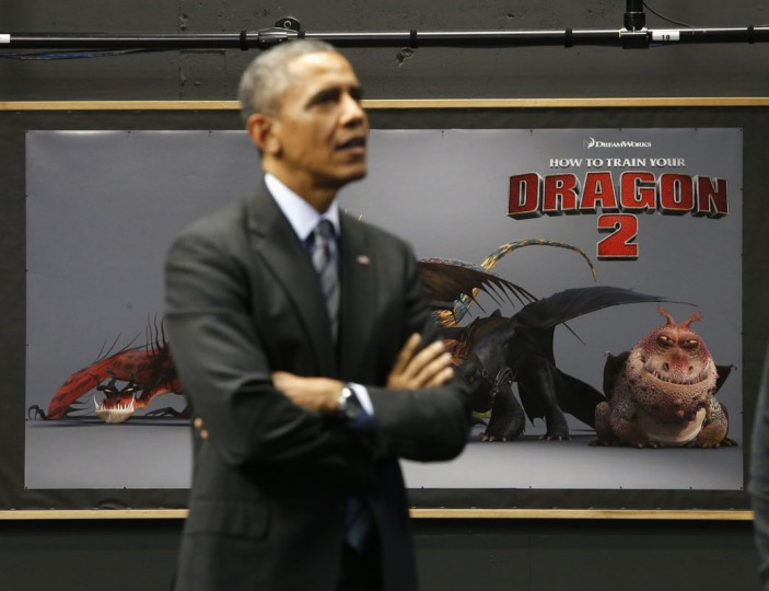 U.S. President Barack Obama stands in front of a promotional poster for the upcoming DreamWorks animation film 'How To Train Your Dragon 2' during a tour of DreamWorks Animation in Glendale, California, November 26, 2013. (REUTERS/Jason Reed)
