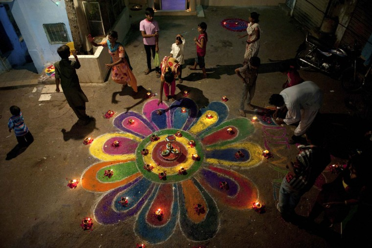 "Members of the Pakistani Hindu community stand around a ""rangoli,"" traditional patterns made from coloured powders, during Diwali celebrations at the Shree Swami Narayan Temple in Karachi, November 3, 2013. Prayers and offerings are made to Hindu deities on Diwali, the annual festival of lights. (Insiya Syed/Reuters)"